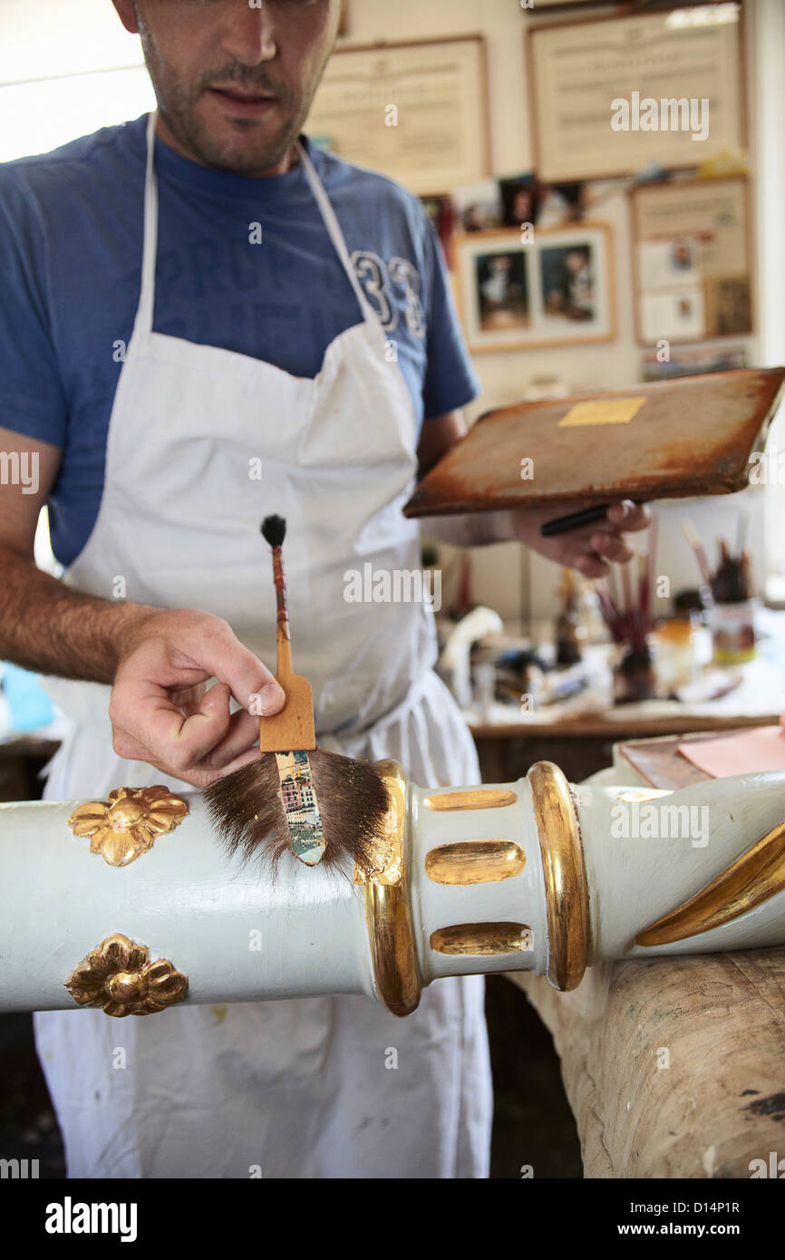 Worker applying gold leaf to pole Stock Photo