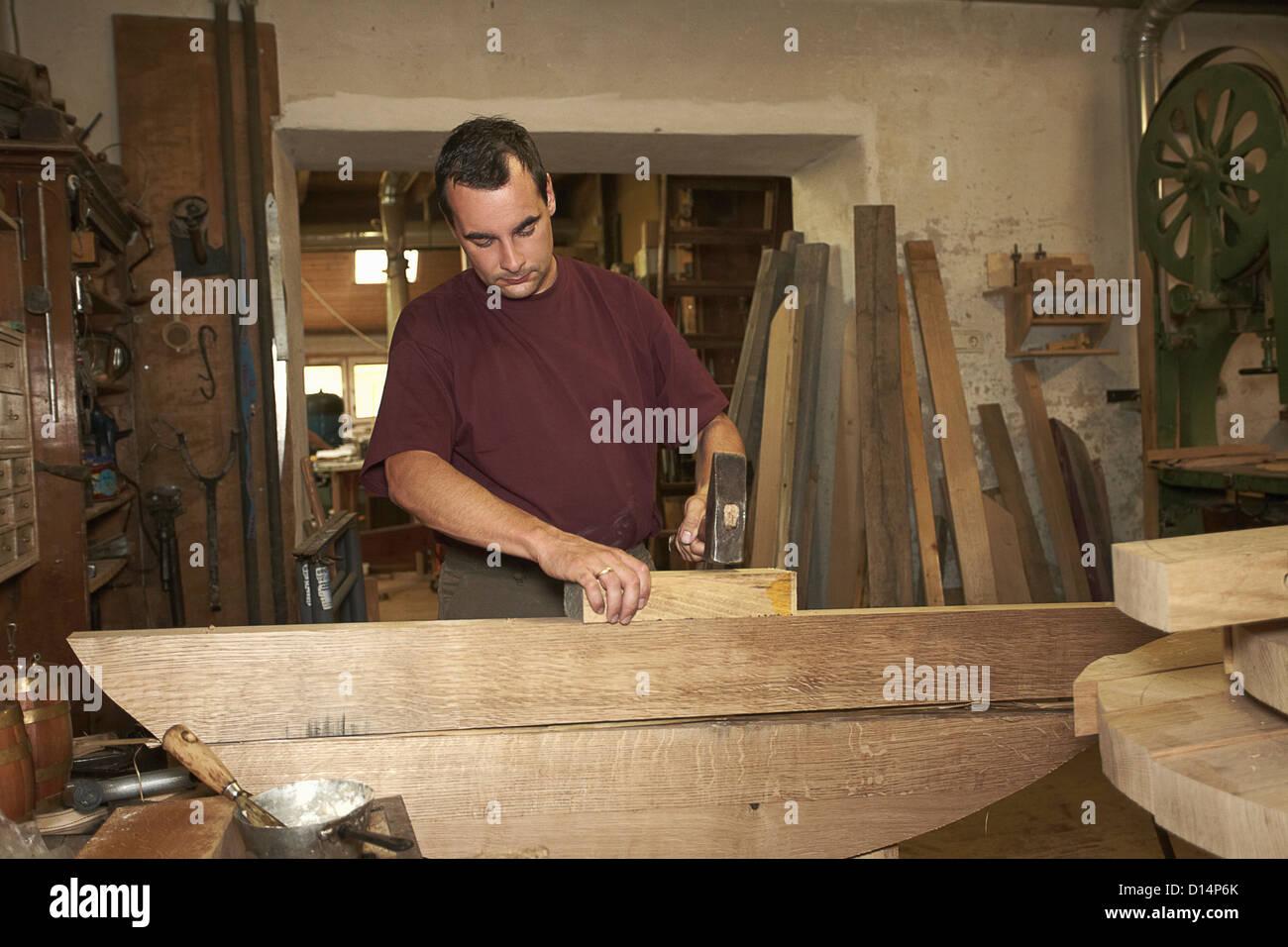 Worker hammering wood in shop - Stock Image
