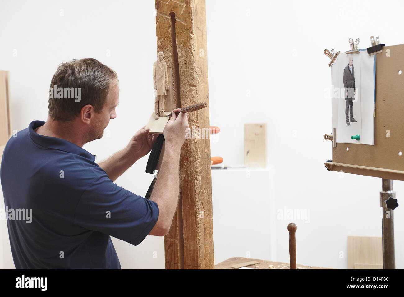 Worker chiseling figure from wood Stock Photo