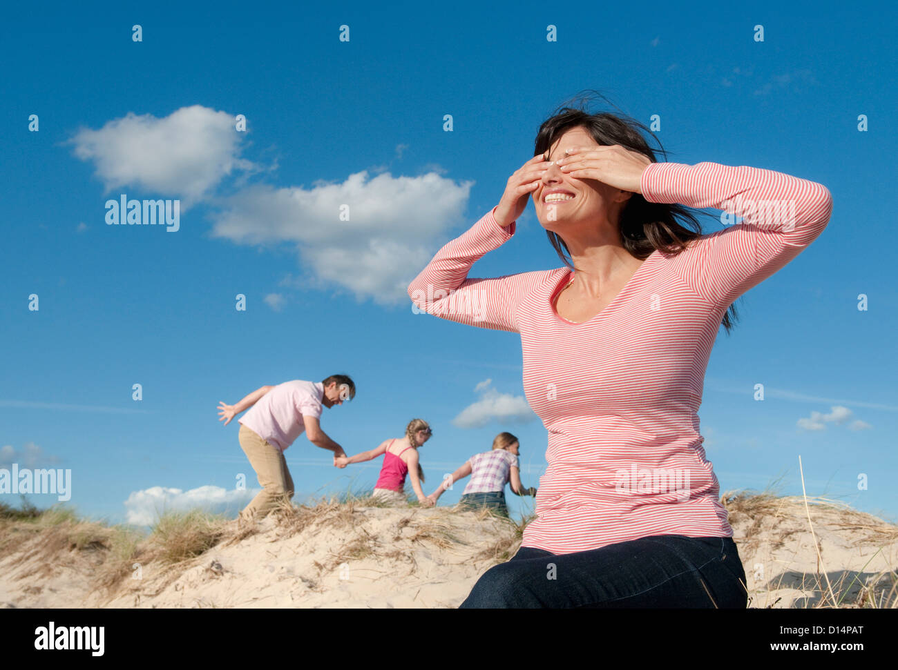 Family playing hide and seek outdoors - Stock Image