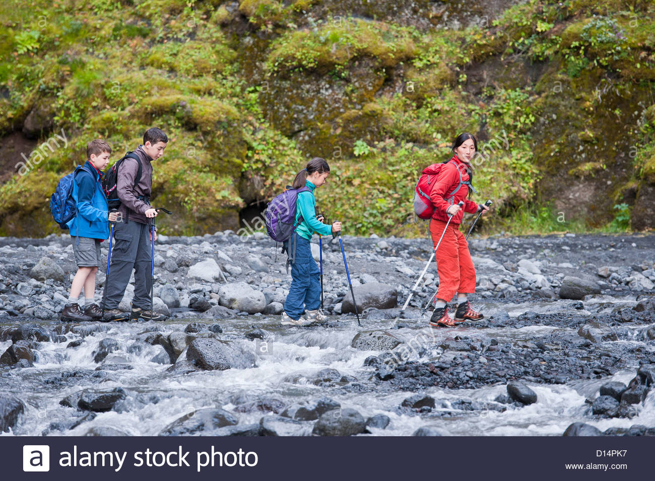 Family hiking rocky river together - Stock Image
