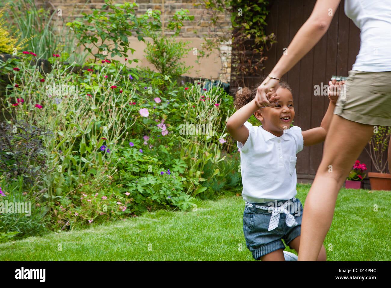 Mother and daughter dancing in garden Stock Photo