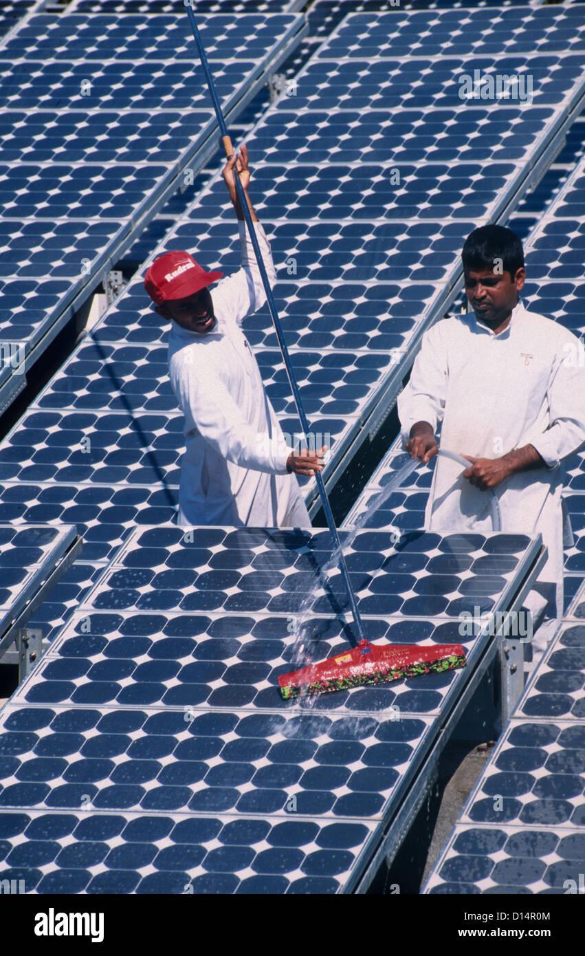 India Rajasthan, men clean solar panel in Brahma Kumari Ashram in Mt. Abu, solar modules a used for own power generation - Stock Image