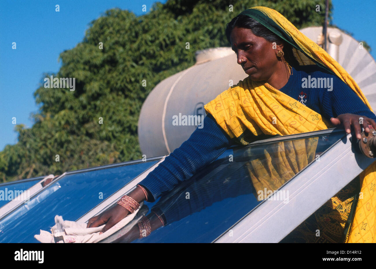 India Rajasthan, woman clean solar collector in Brahma Kumari Ashram in Mt. Abu, solar collector is used to get - Stock Image