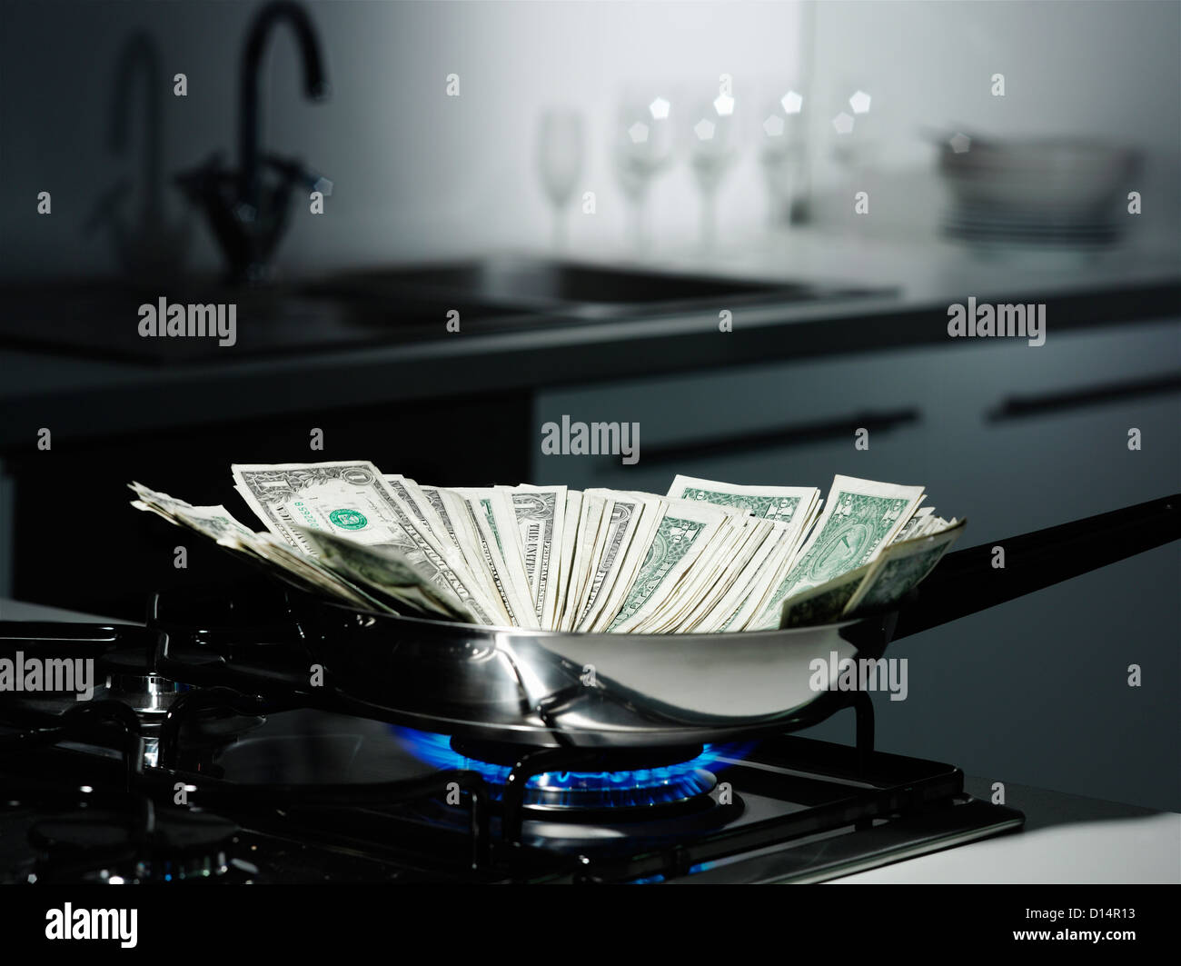 Dollar bills in frying pan on stove - Stock Image