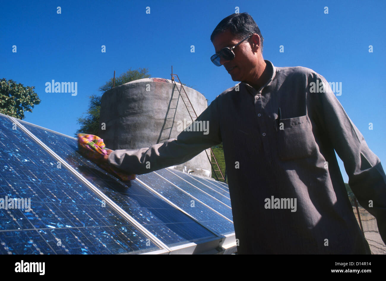 India Rajasthan , man clean solar panel of solar powered water pump to fill water in tank, project barefoot college - Stock Image