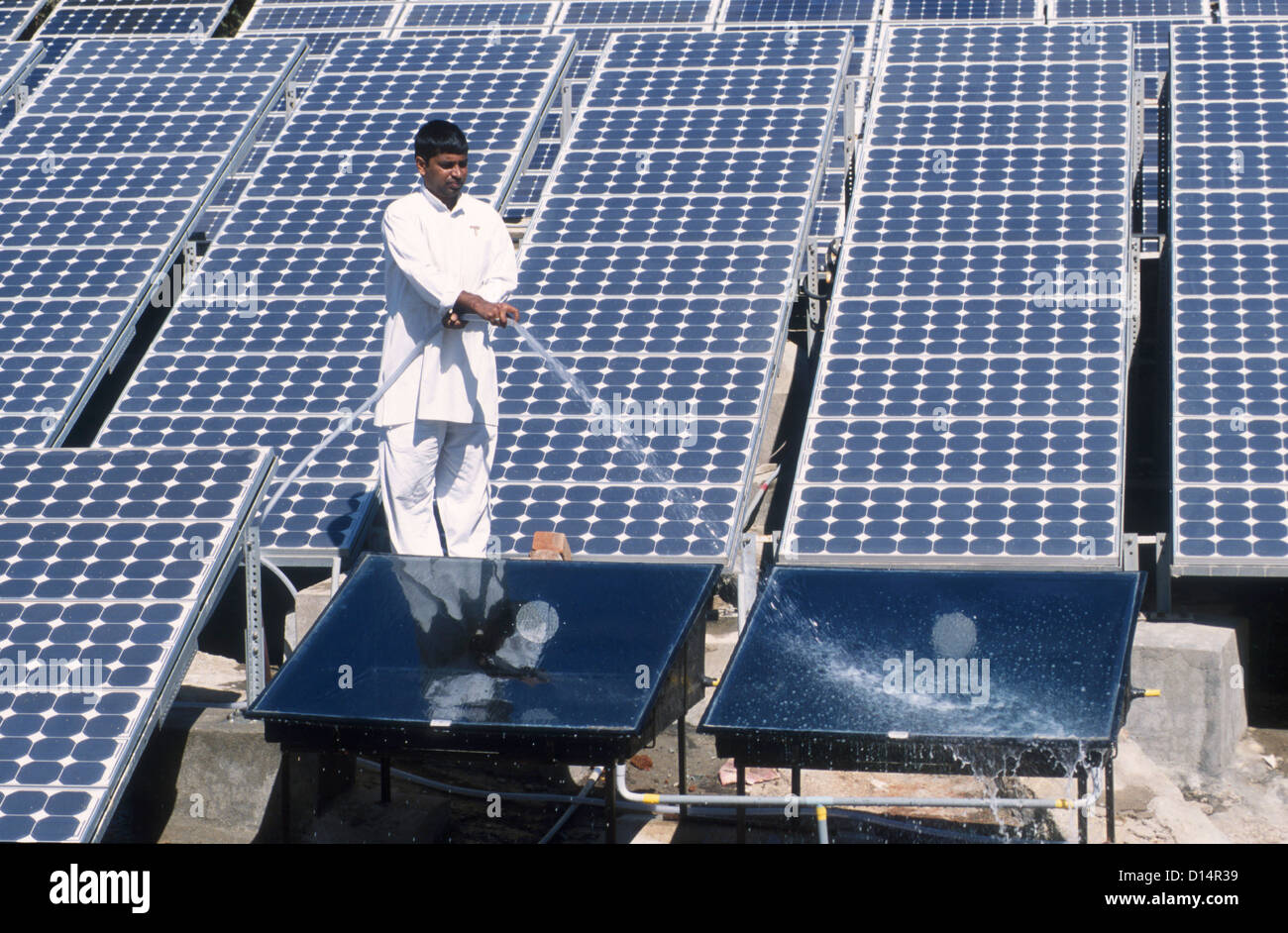 India Rajasthan, man clean solar collector in Brahma Kumari Ashram in Mt. Abu, solar collector is used to get heated - Stock Image