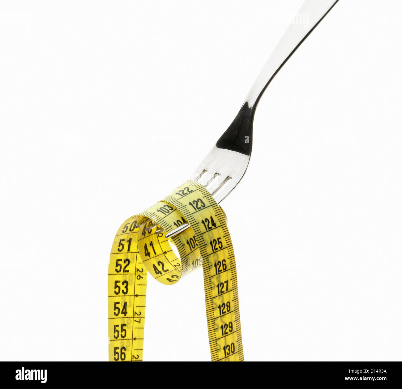 Measuring tape coiled on fork - Stock Image