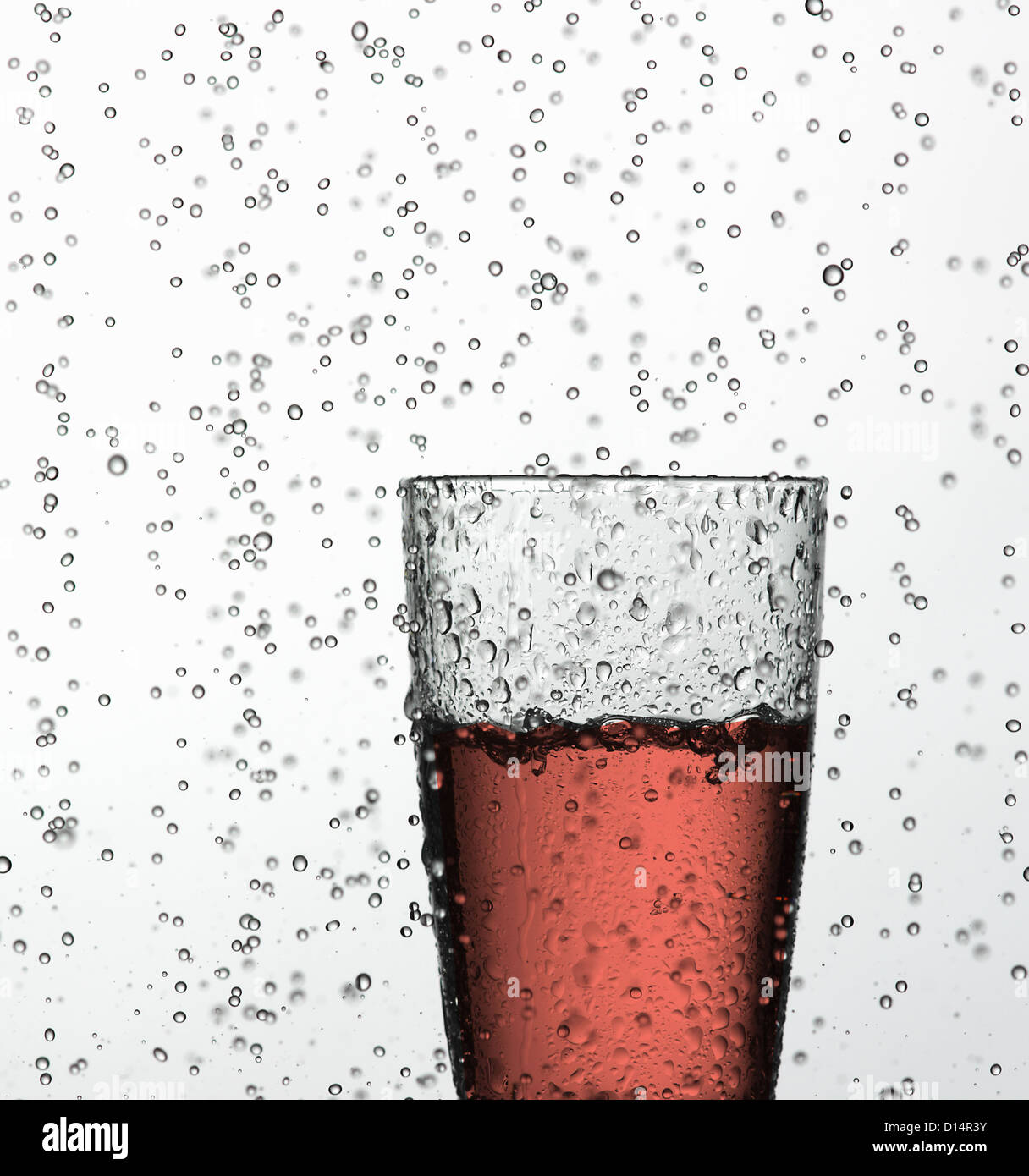 Glass of juice in water drops - Stock Image