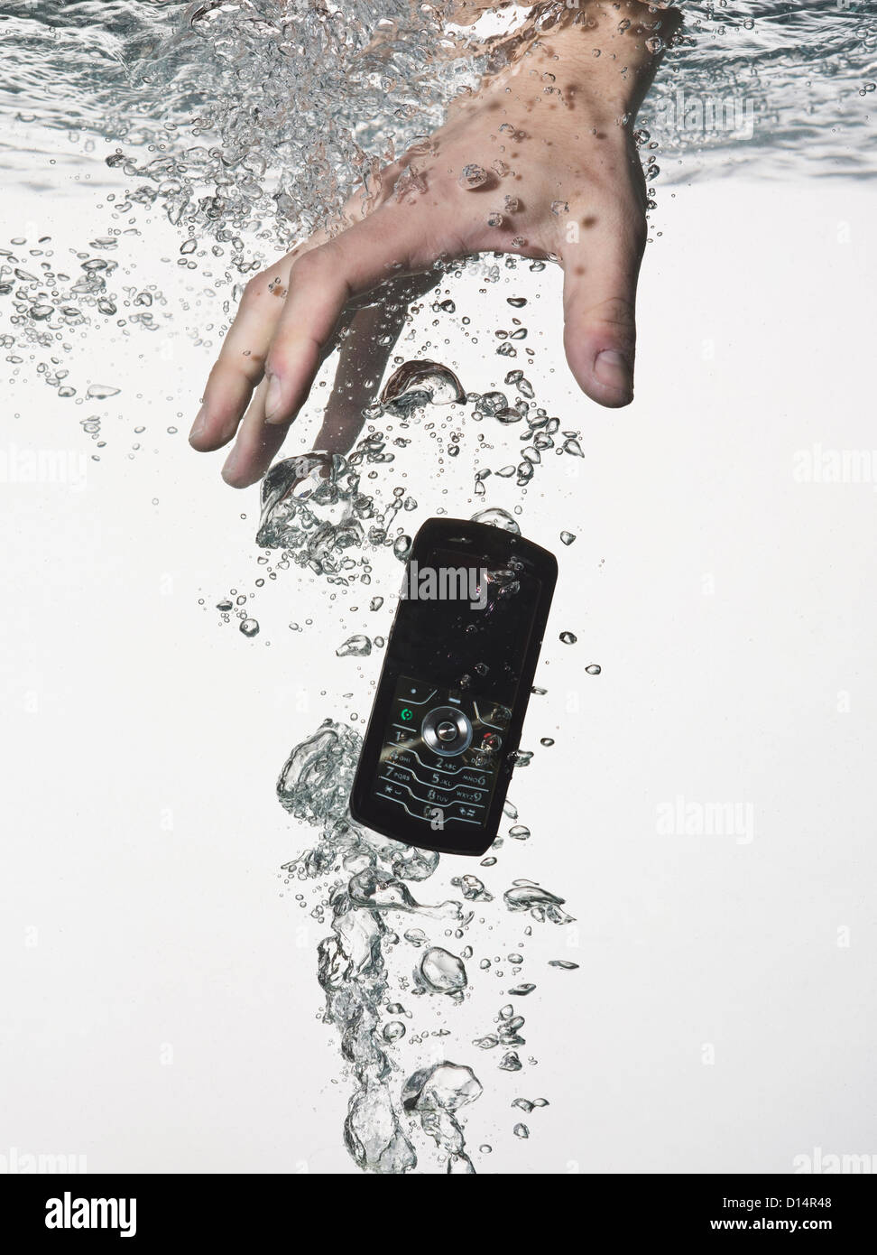 Hand grasping cell phone in water - Stock Image
