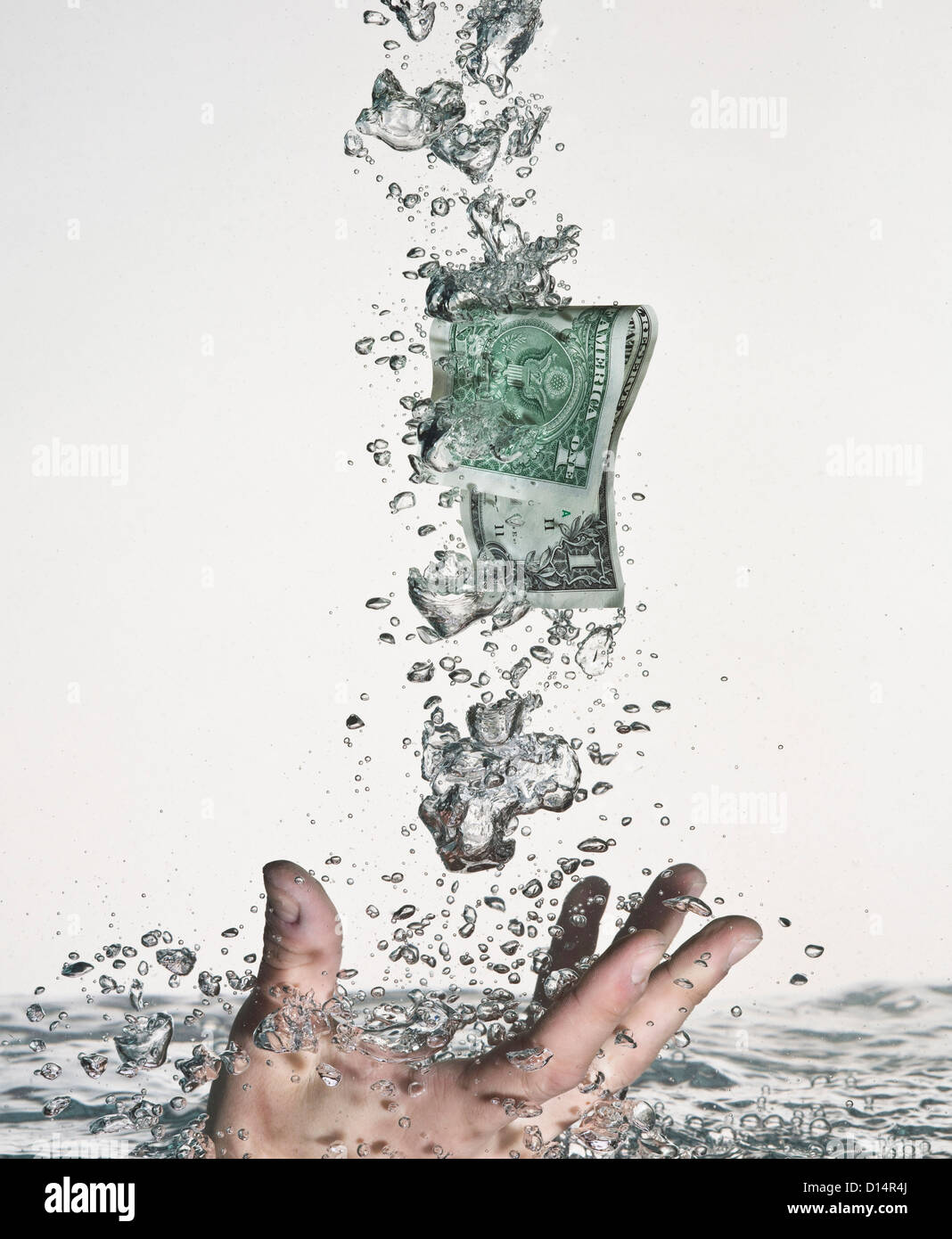 Hand grasping dollar bill in water - Stock Image