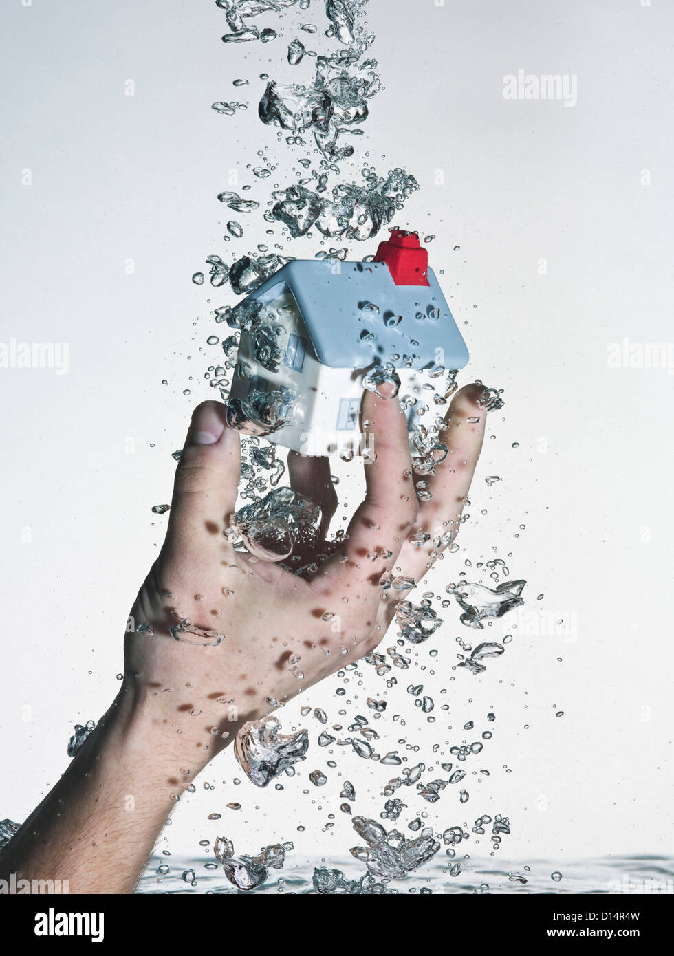 Hand grasping model house in water - Stock Image