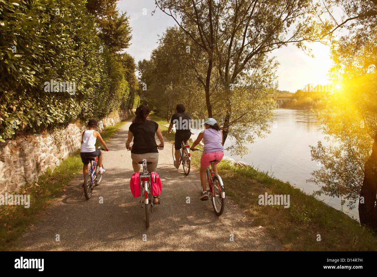 Family riding bicycles by river bank - Stock Image