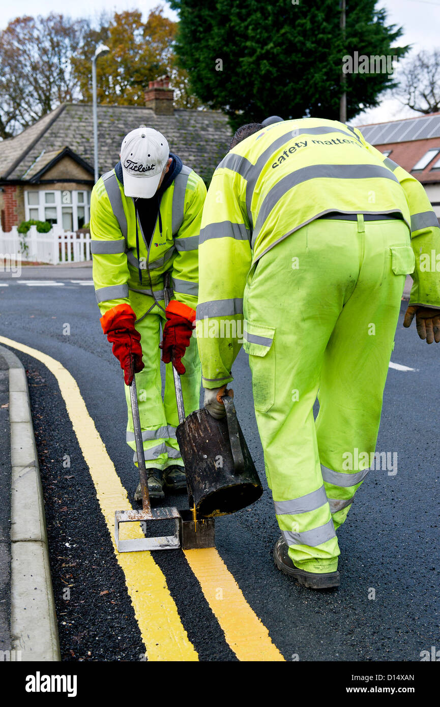 Highway maintenance workers laying down double yellow lines. - Stock Image