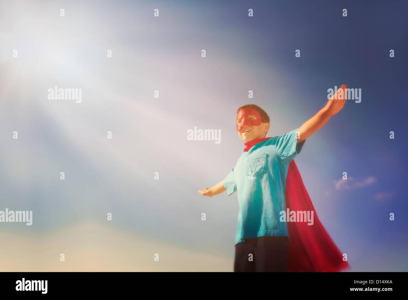 USA, New Jersey, Jersey City, Boy (6-7) in superhero costume under blue sky - Stock Image