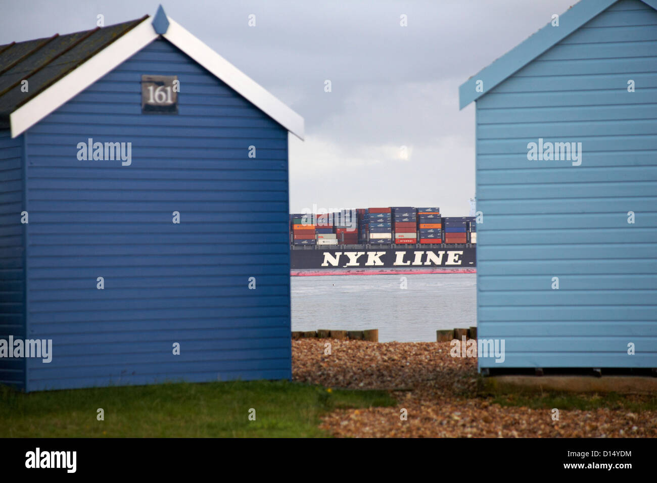 Container ship NYK Lines seen through gap between two beach huts at Calshot, Hampshire in November - Stock Image