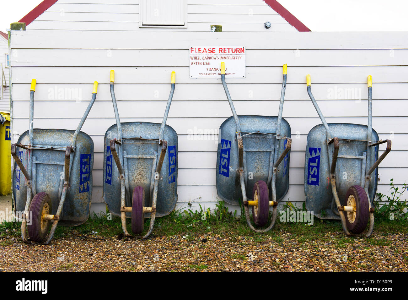 Wheelbarrows leaning against a wooden fence at Tollesbury Saltings. - Stock Image