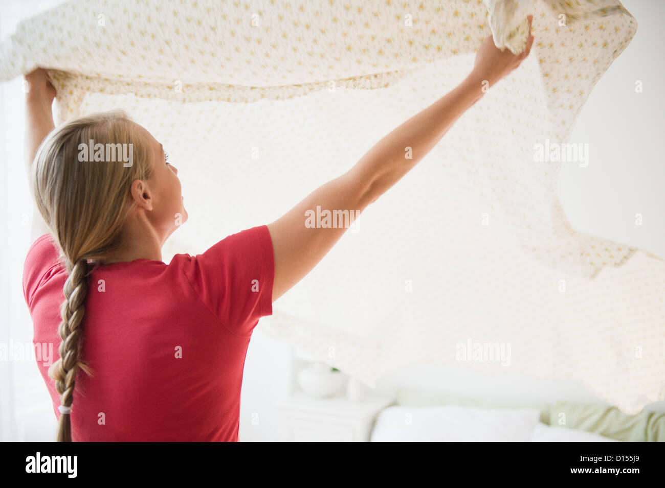 USA, New Jersey, Jersey City, Young woman preparing clean sheet for bed - Stock Image