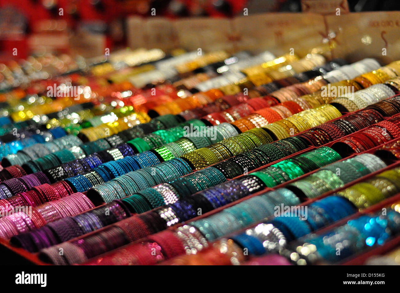 Lines of multi-coloured bracelets at a Christmas market stall Cologne - Stock Image