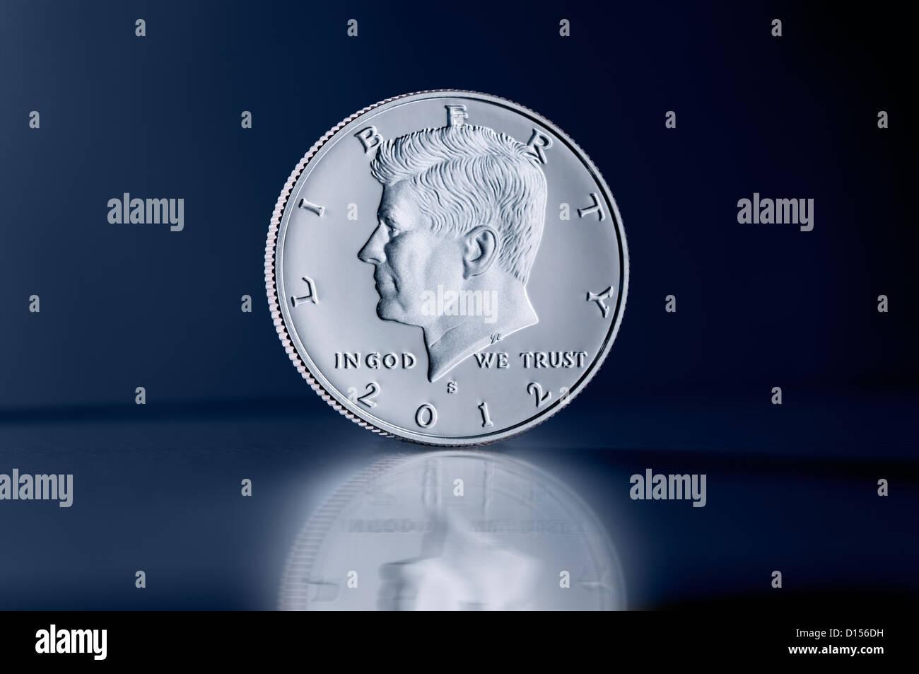 Upright Kennedy Half Dollar coin against dark background - Stock Image