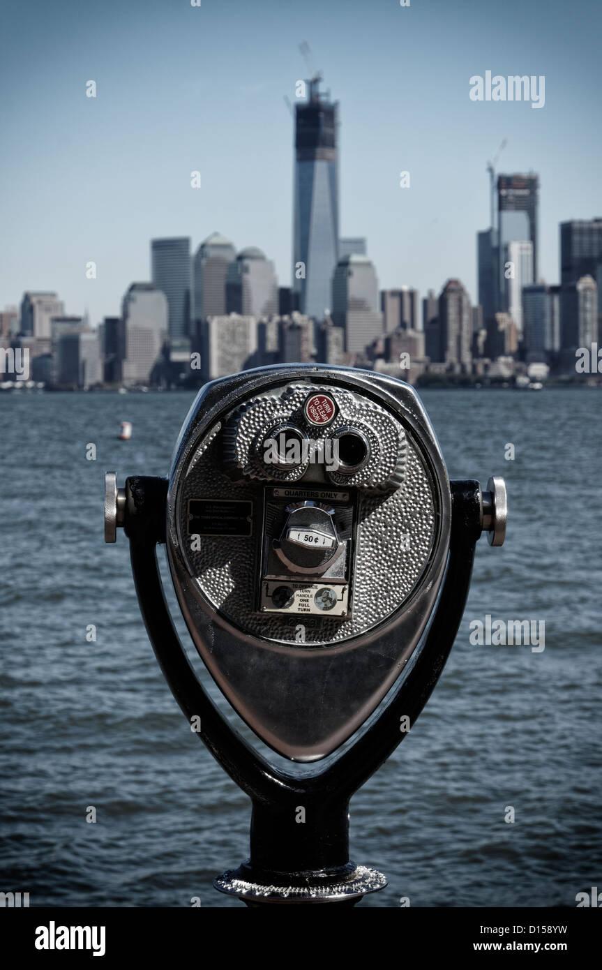 Coin operated binocular on Liberty Island towards Manhattan Skyline, NYC - Stock Image