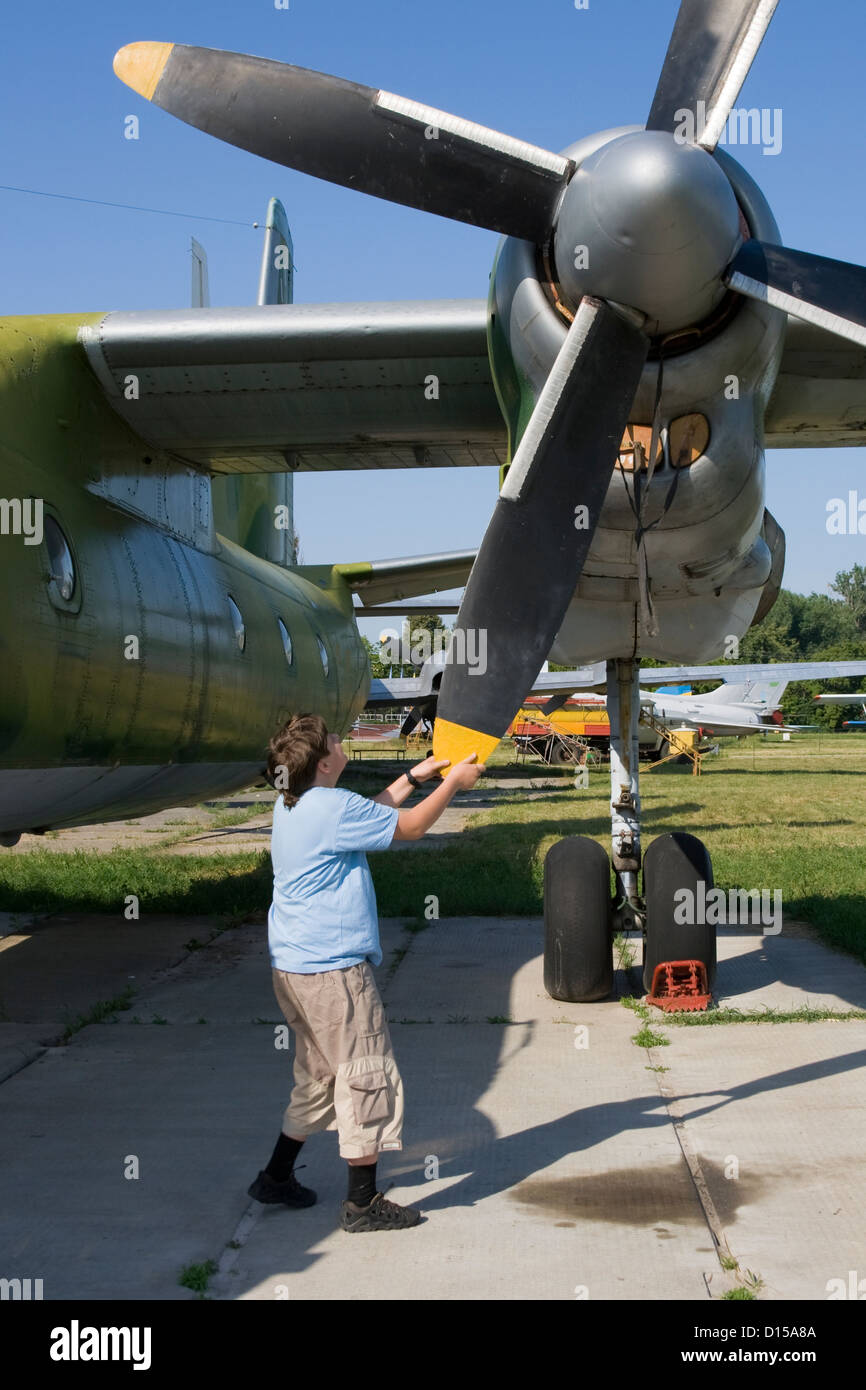 A boy attempts to rotate huge plane air screw - Stock Image