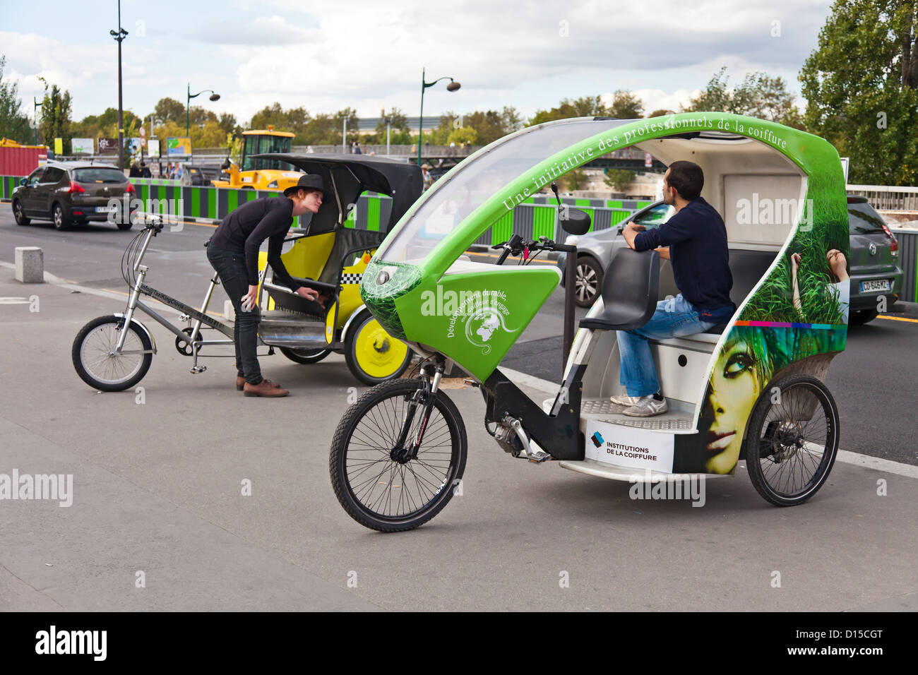 Two types of cycle rickshaw and their drivers in central Paris, France. Eco-friendly transport. Street scene. Two - Stock Image