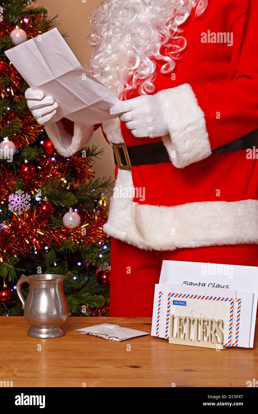 Santa Claus reading a letter at his home in the North Pole - Stock Image