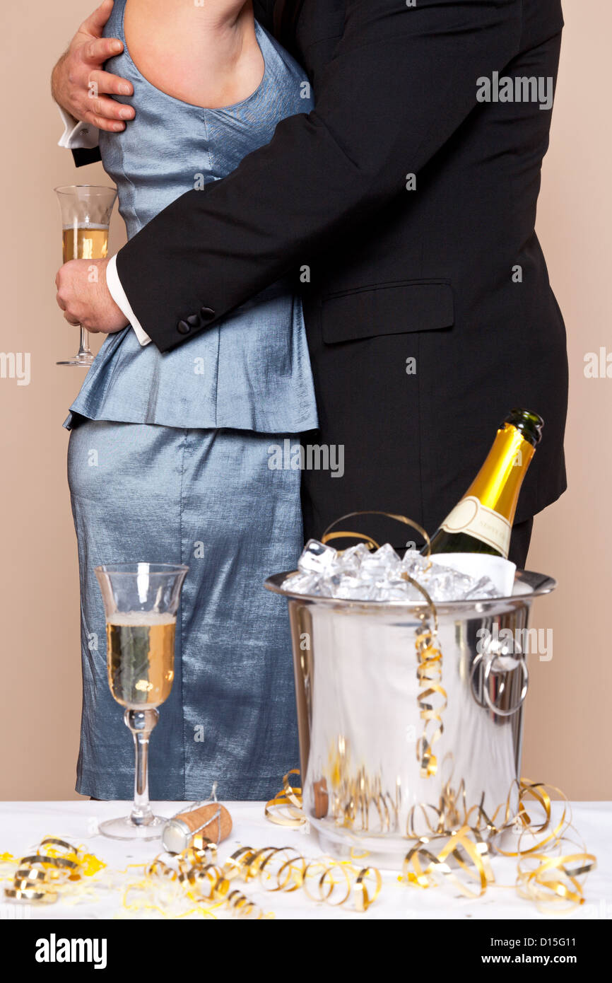 a couple embracing with glasses of champagne at a party good image for new years eve wedding or anniversary themes