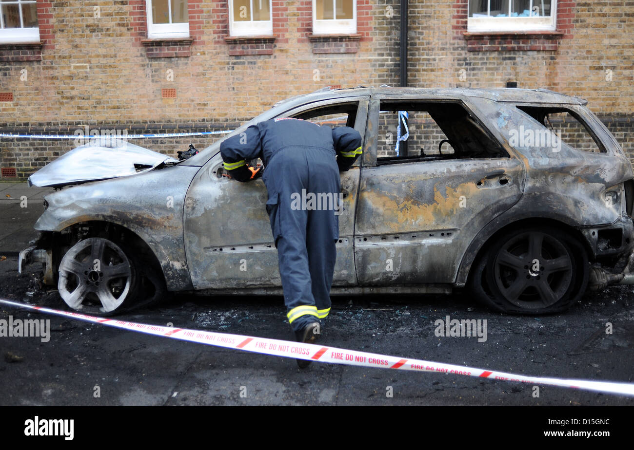 A Fire Investigation Officer checks out the burnt out cars in Connaught Road Hove this morning .  Brighton Sussex - Stock Image