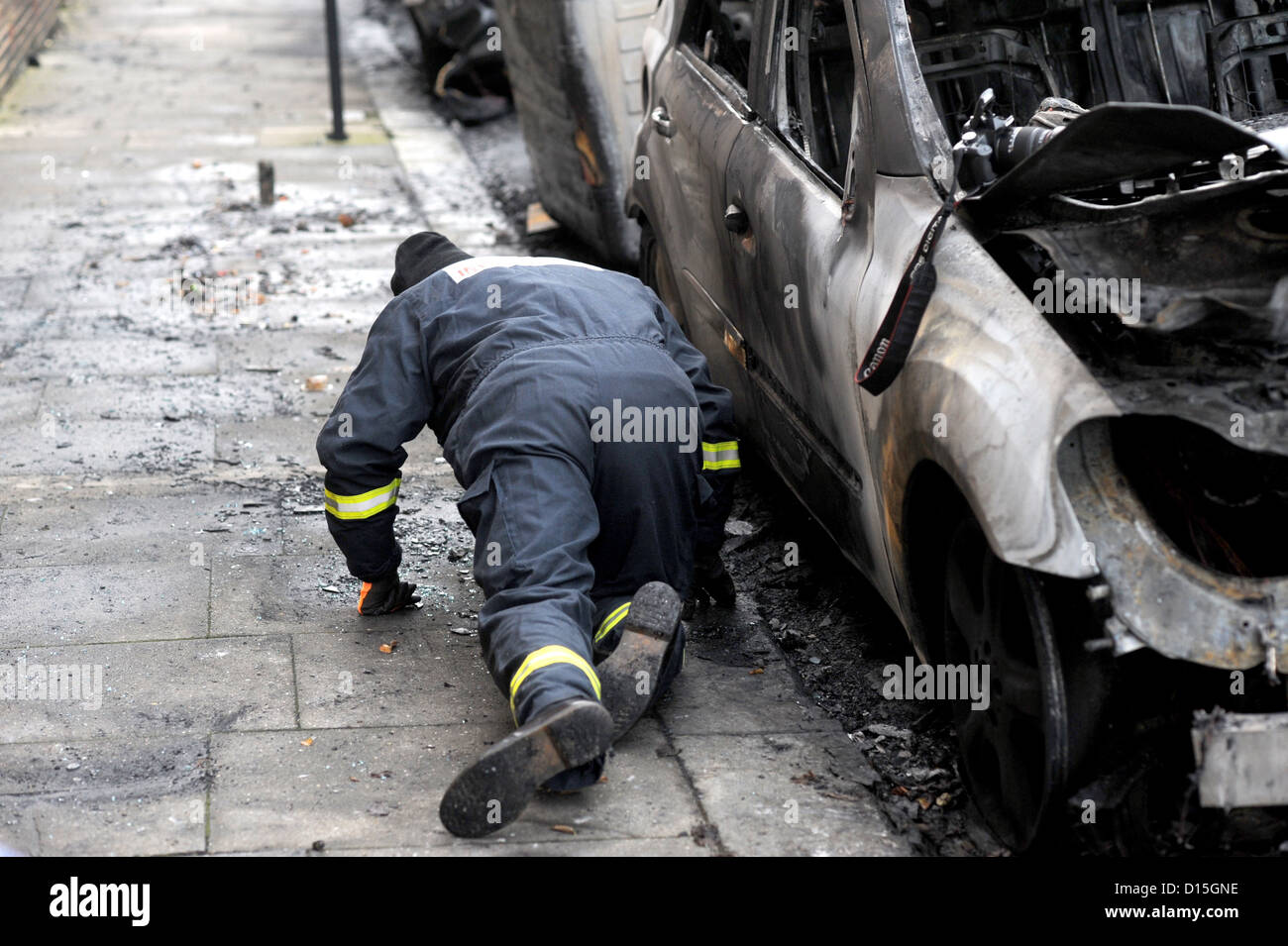 A fire investigation officer on hands and knees looking at burnt out cars in Connaught Road Hove - Stock Image