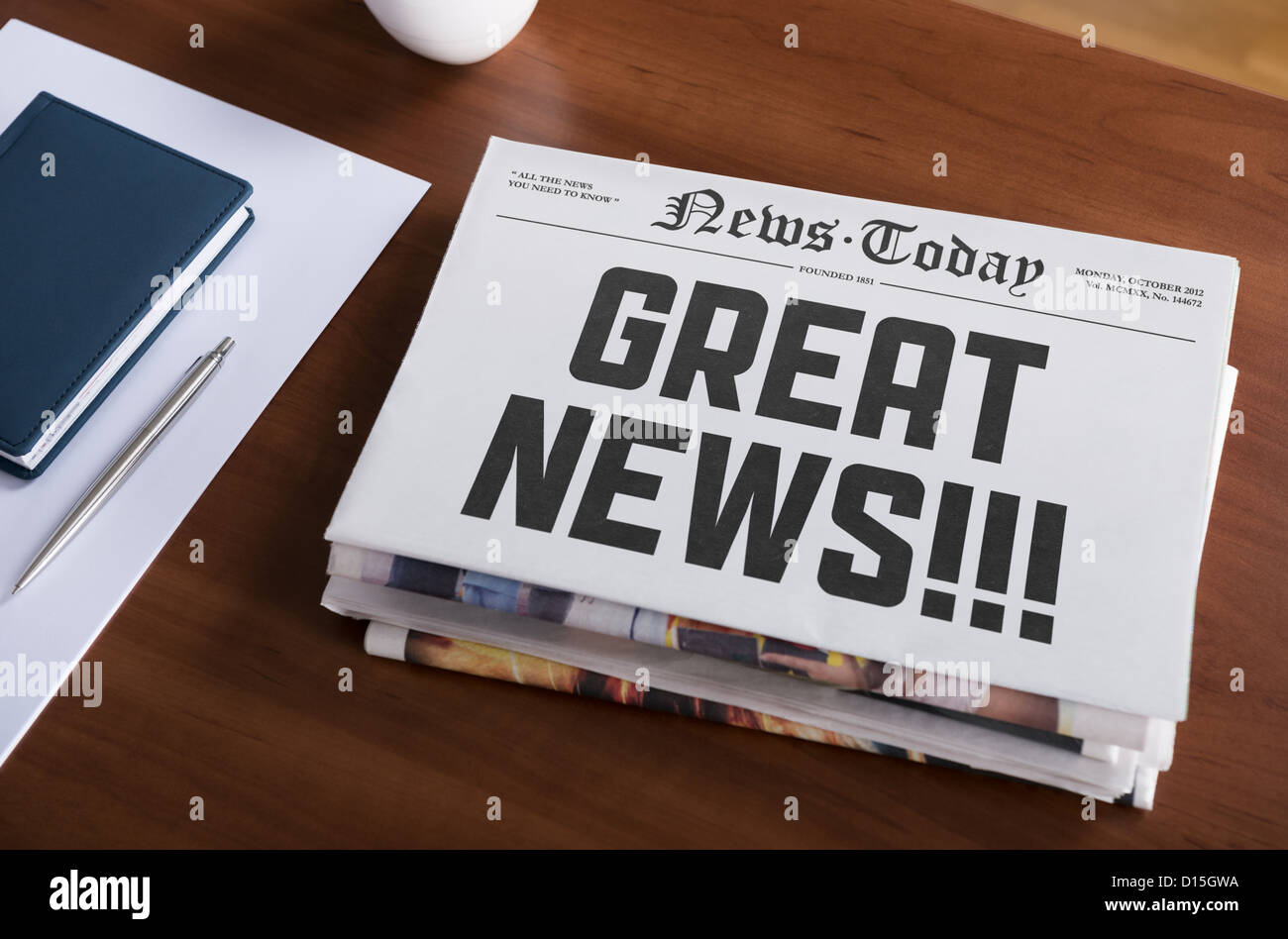 Newspaper with hot topic 'Great news' lying on office desk. - Stock Image