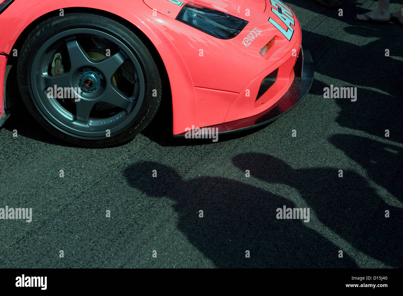 The shadows of people looking at the front of a pink Mclaren F1 racing car at a car show. Stock Photo