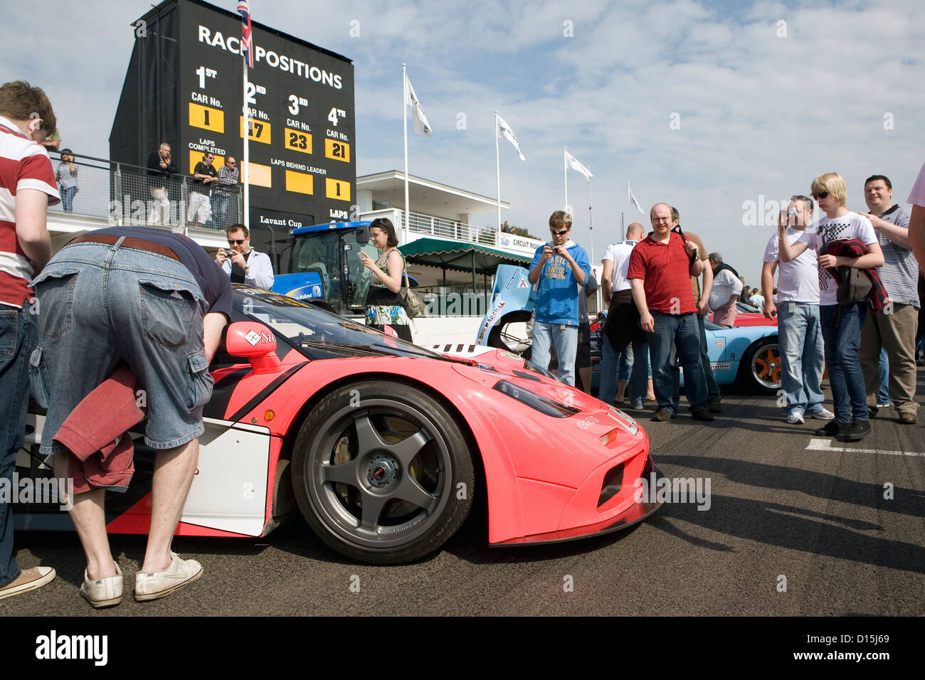 A crowd of people looking at a pink supercar at a car show. Stock Photo