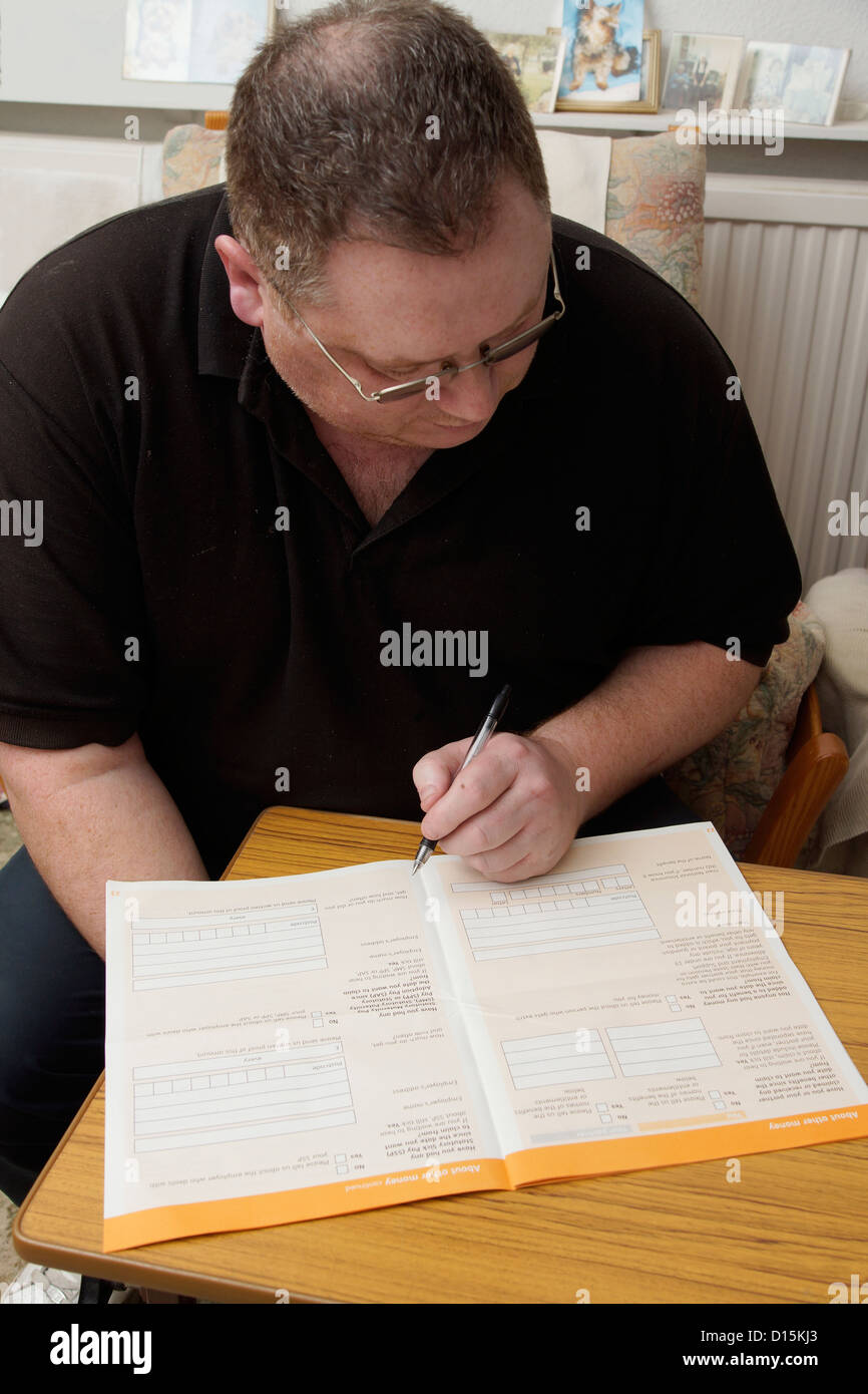 Man filling in an application form to claim for benefits - Stock Image