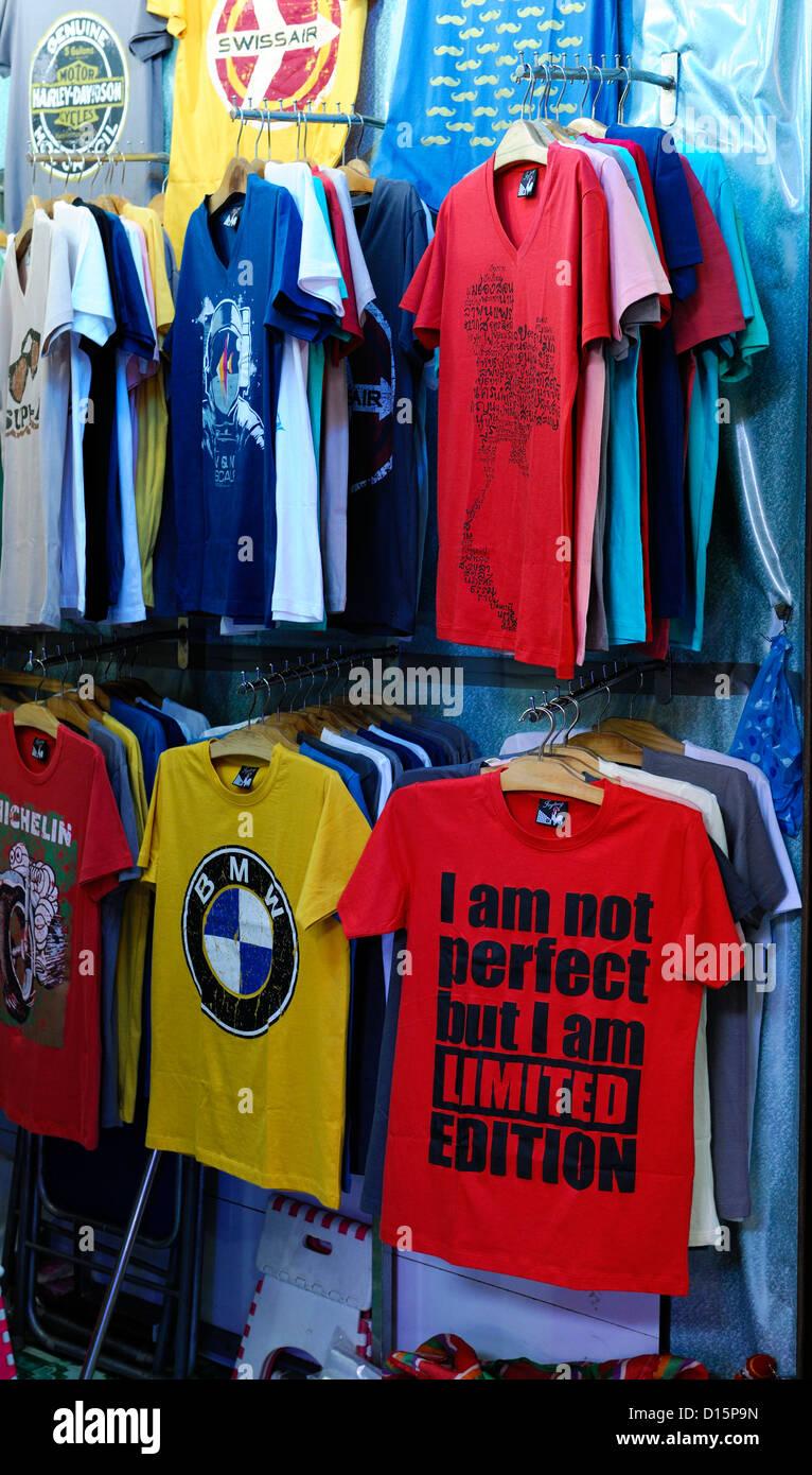 07706856 souvenir souvenirs trinkets objects market stall vendor chatuchak weekend  market bangkok thailand funny humorous tee shirts tops