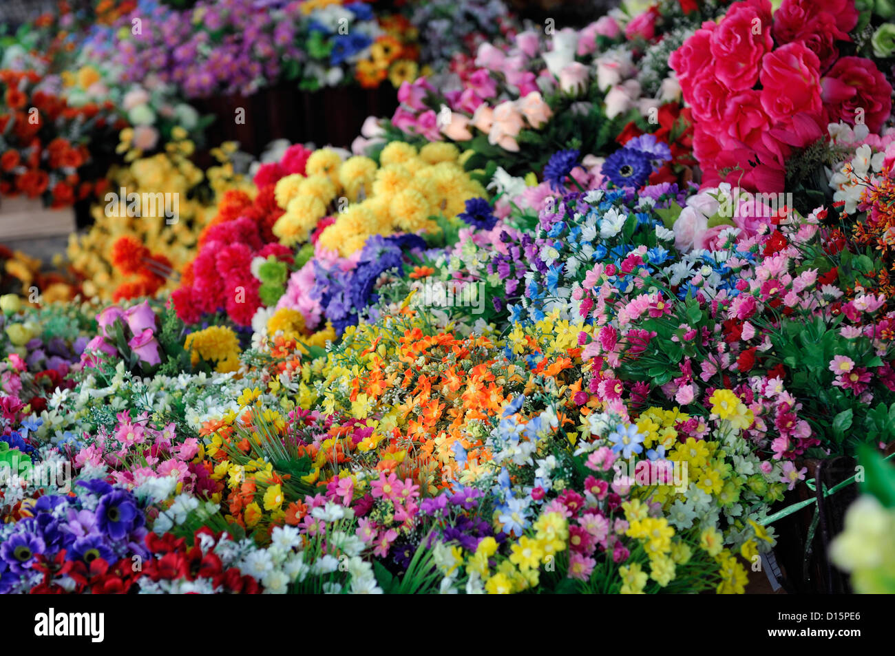 plastic multi coloured colored flowers on sale stand market stall vendor chatuchak weekend market bangkok thailand - Stock Image
