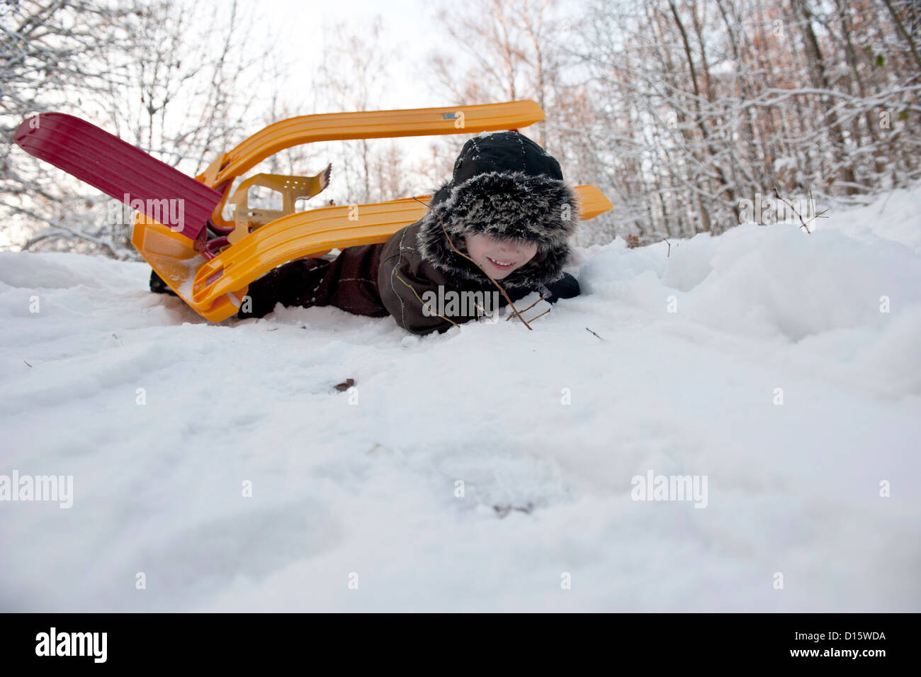Young boy doing an overturn with a snow sledge - Stock Image