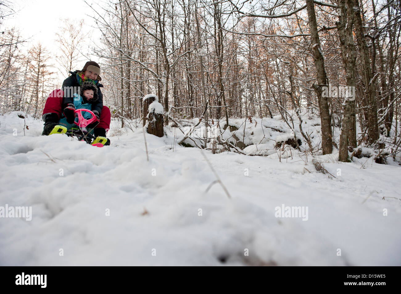 Mother and child going downhill on a snow sledge - Stock Image