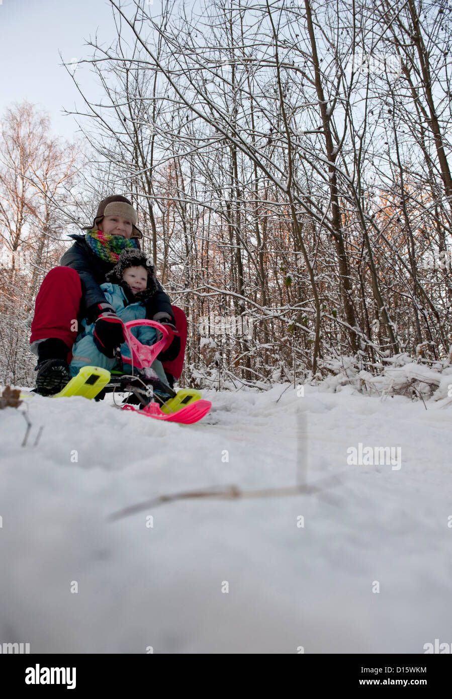 Mother and child having fun with a snow sledge - Stock Image
