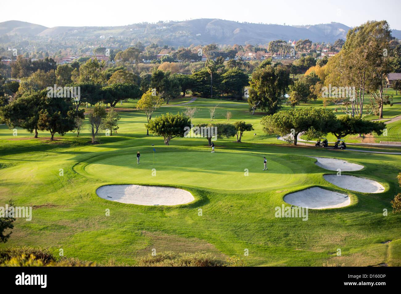 Three golfers putt on a green at the San Juan Hills golf course in San Juan Capistrano, California. - Stock Image