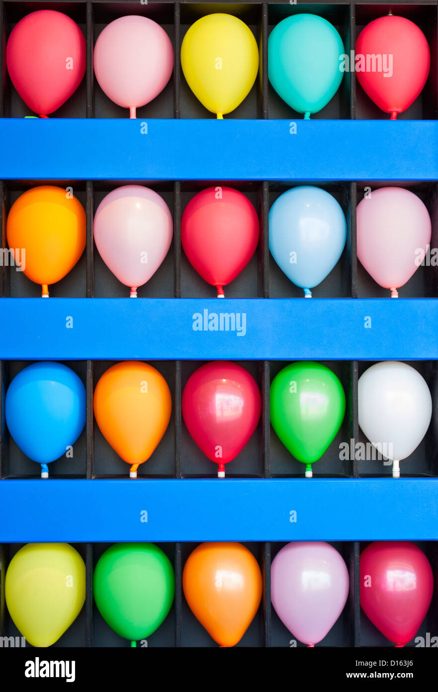 A blue wall case with colorful balloons. Photo is of a boardwalk arcade game. Only the wall case and balloons are - Stock Image