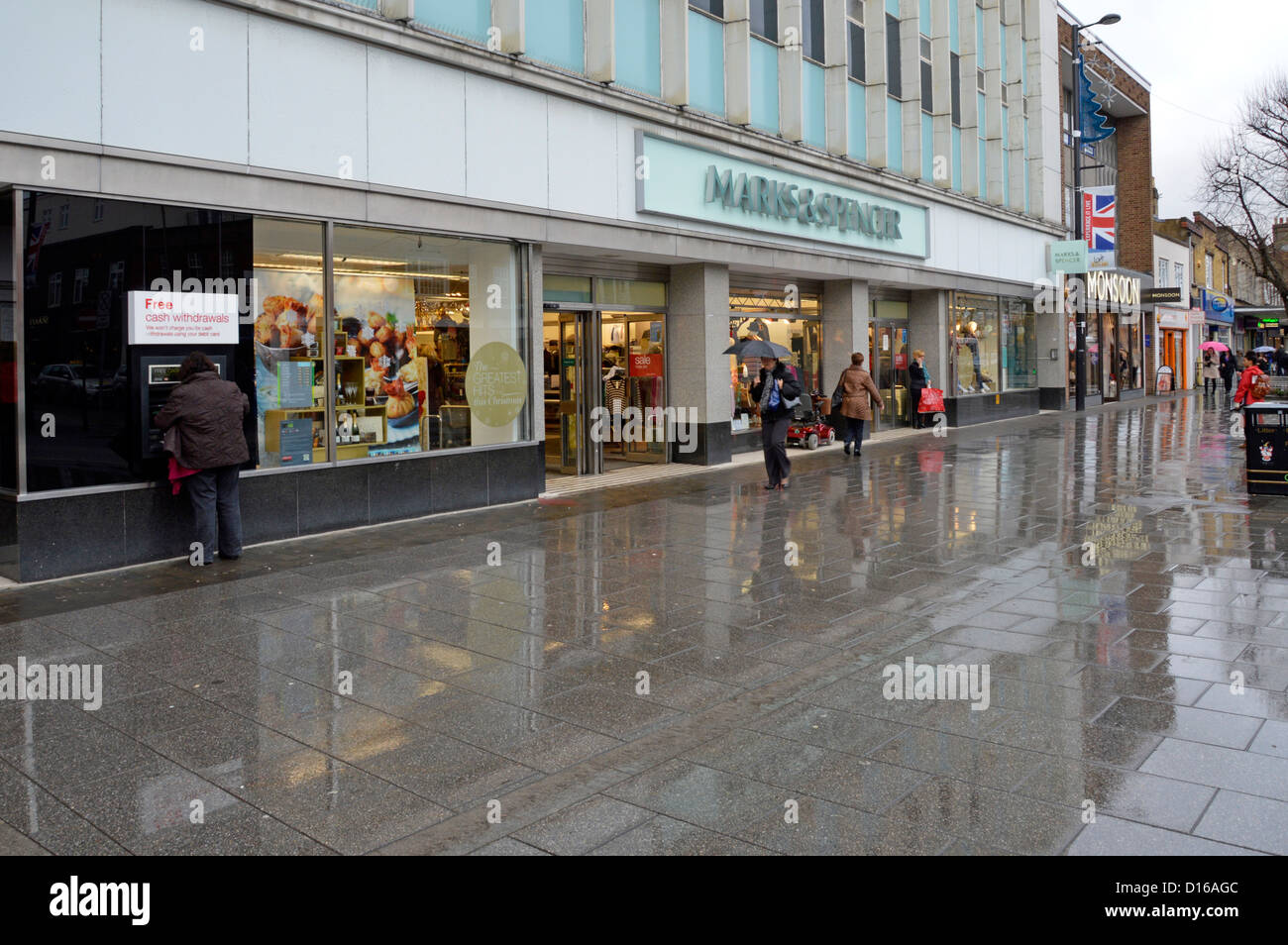 Raining on shopping high street outside Marks and Spencer store - Stock Image