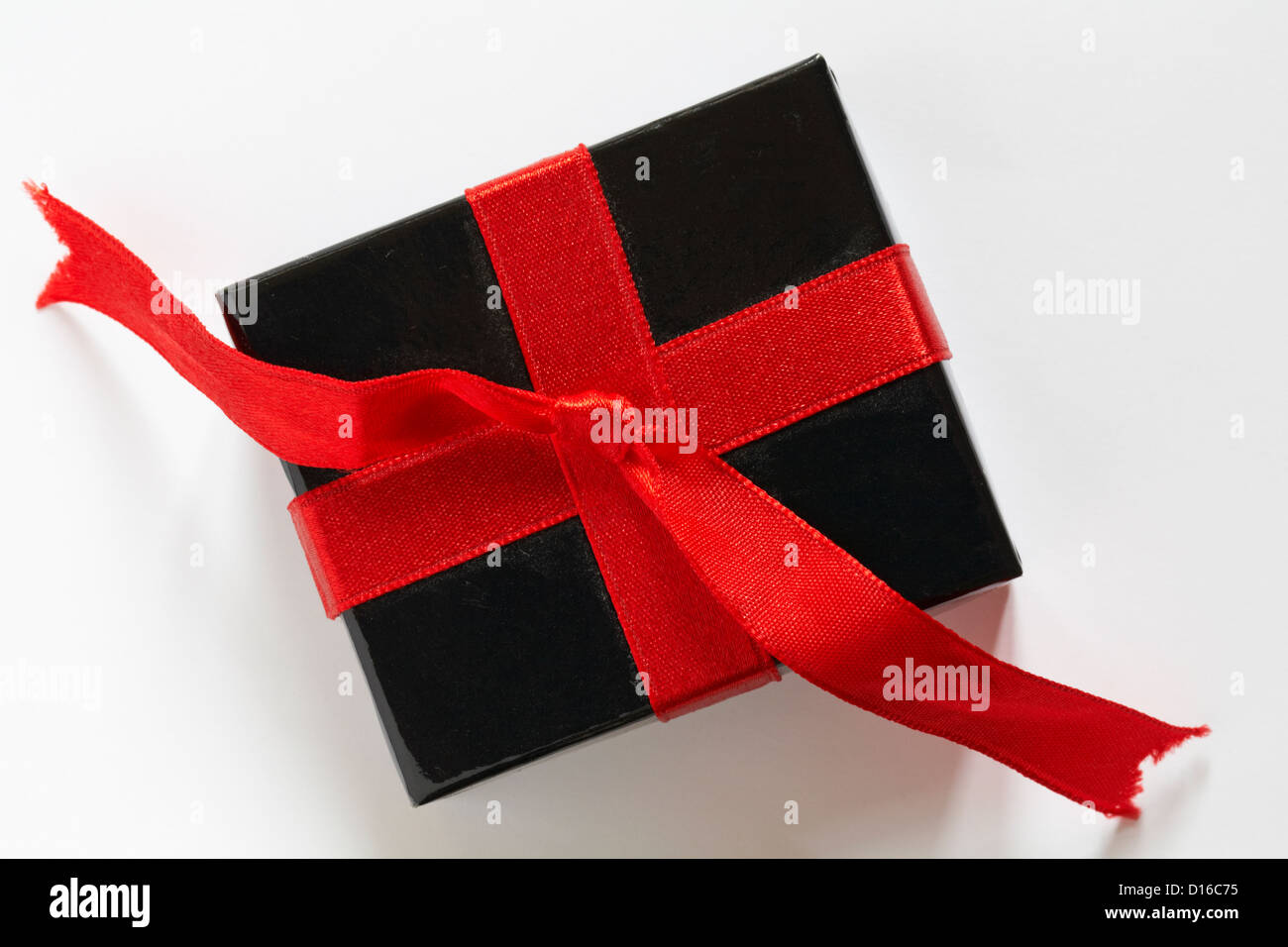 Black gift box with red ribbon isolated on white background - Stock Image