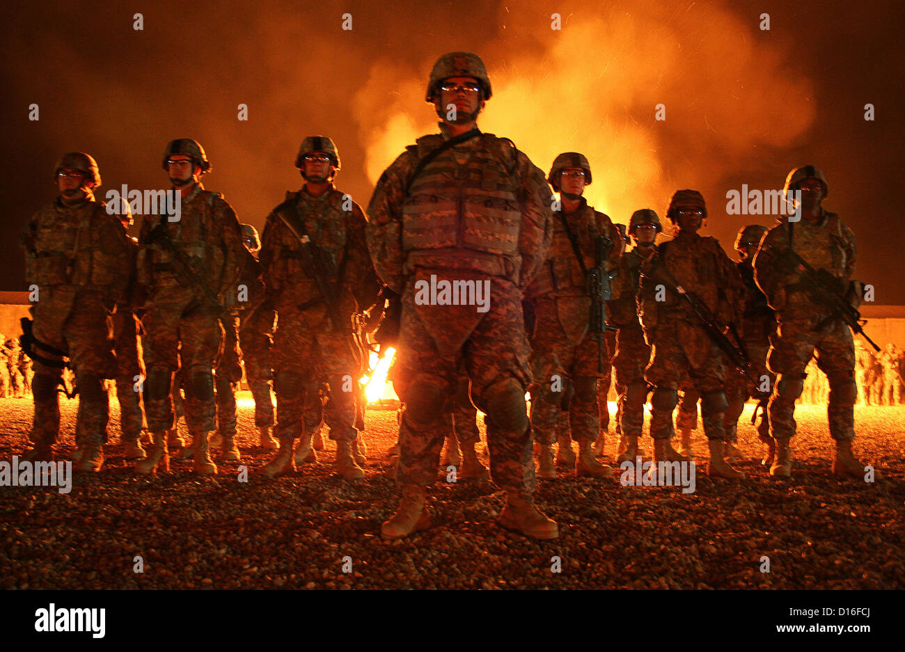 A bonfire lit the sky in Babil Province, Iraq March 3, 2009 as 22 Army graduates were welcomed into the ranks of - Stock Image