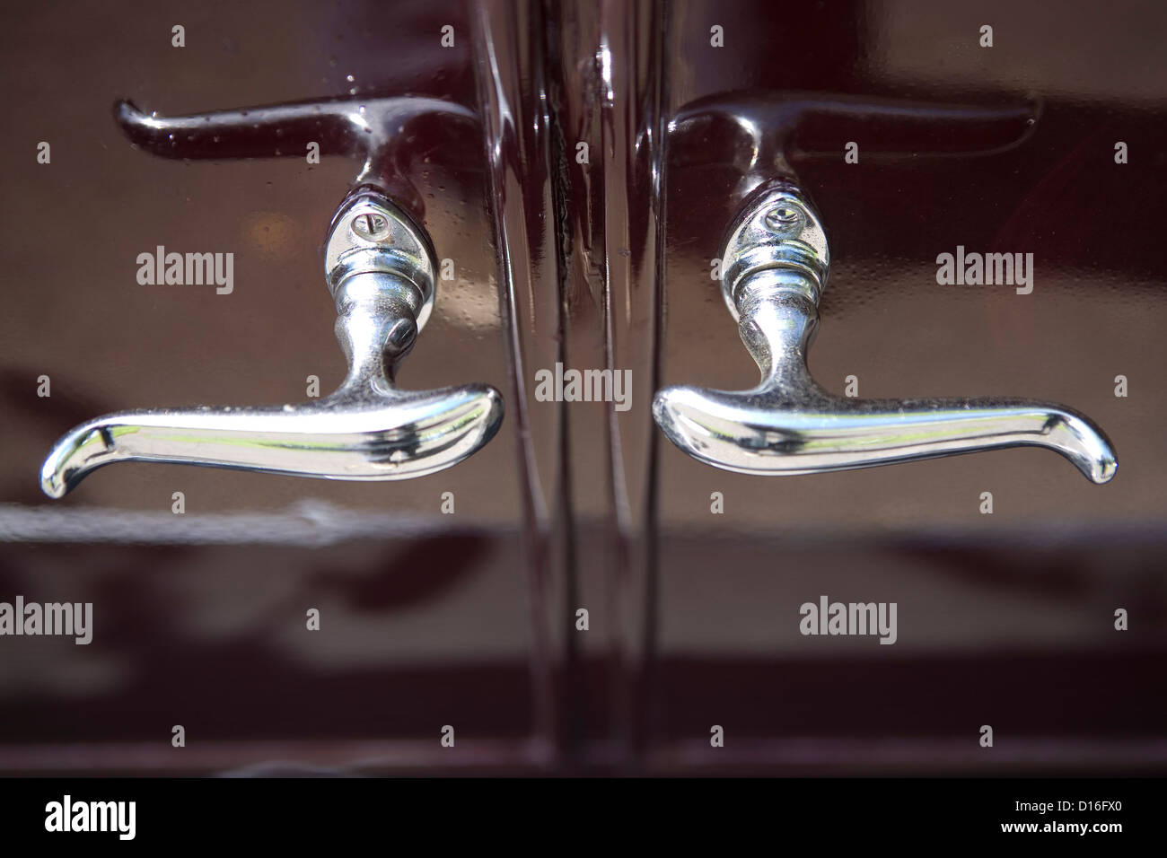 Chrome door handles on the side of a vintage car. - Stock Image