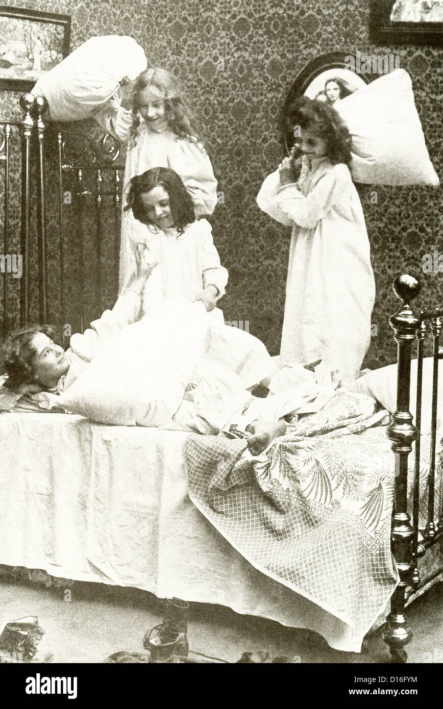 This vintage photograph shows four girls having a pillow fight in 1917. - Stock Image