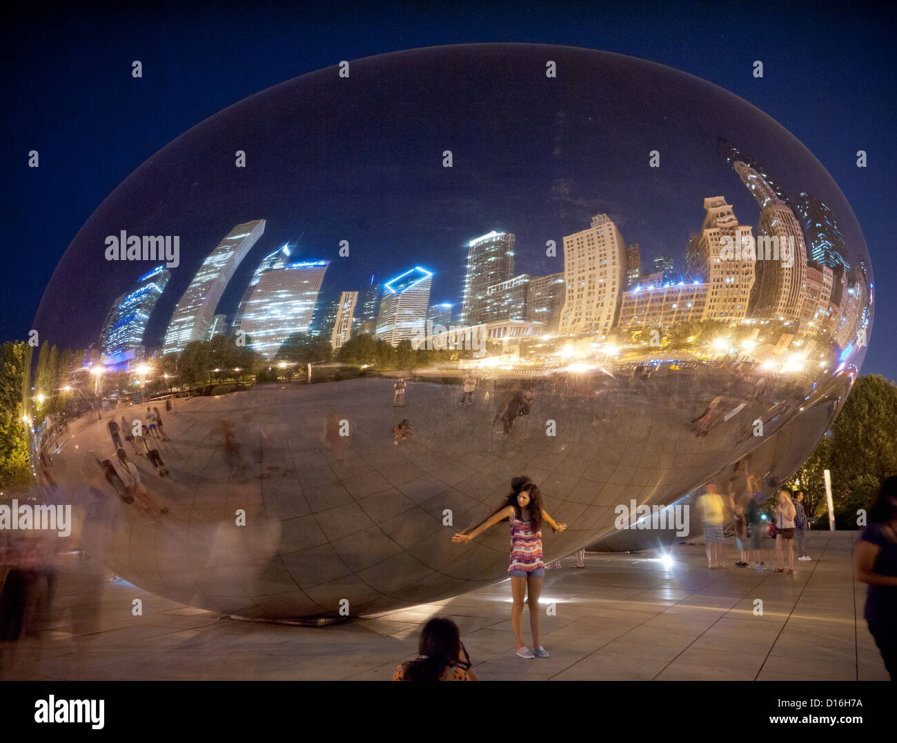 Carrying the world on your back.  A pretty model at Cloud Gate (The Bean) at night in Millennium Park in Chicago, - Stock Image