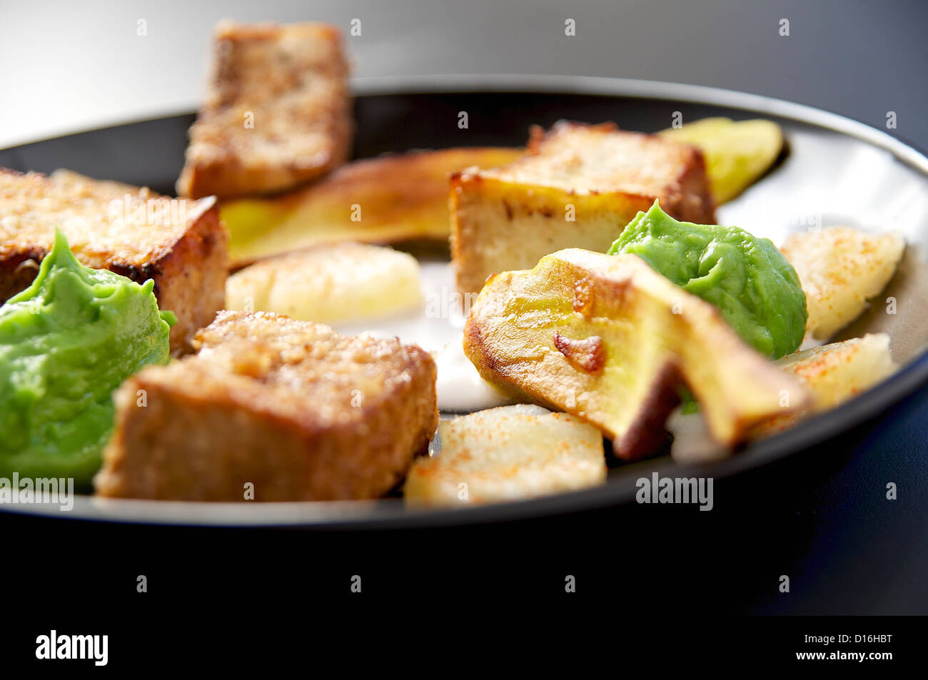 Tofu Medallions with Chili Dusted Pineapple, Avocado Cream and Browned Plantain. - Stock Image