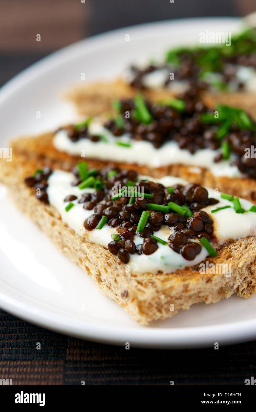 A delicious lunch with beluga lentils on garlic soy yogurt. It would also make lovely appetizers or finger food Stock Photo